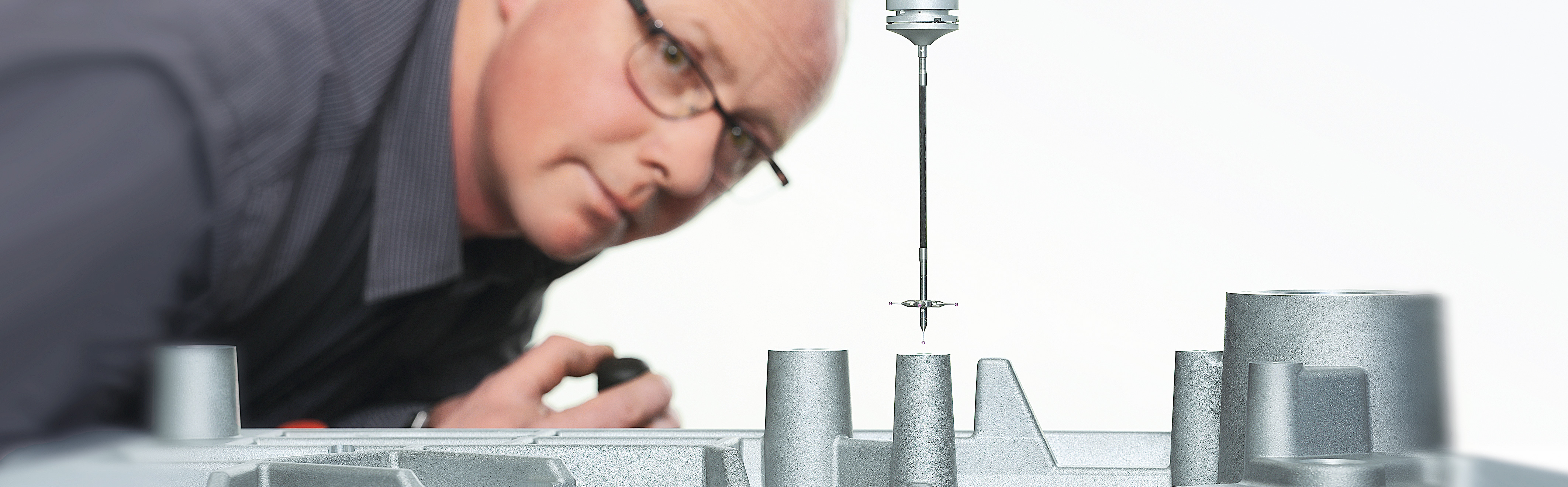 SAHM employee of the quality management looking at a part of a measuring machine